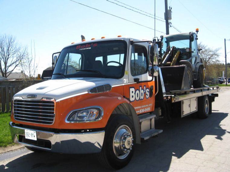 serving guelph & surrounding area since 1981 [orange and white tow truck]